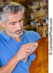 Man polishing string instrument