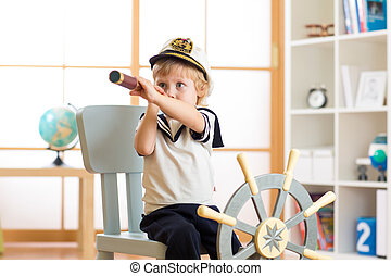 Kid boy dressed like a captain or sailor plays on chair as ship in his room. Child looks through telescope.