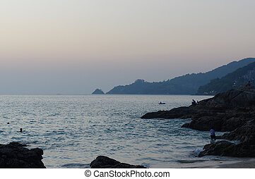 Beautiful sunset at the rock beach in Patong, Phuket island, Thailand