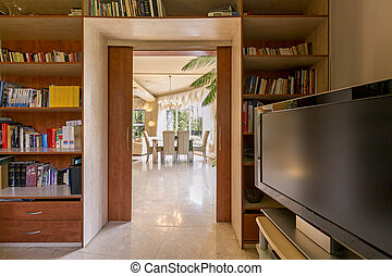 Home office with bookstand, TV set and view of dining room