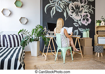 Woman in her study space - Young woman reading a book in her...