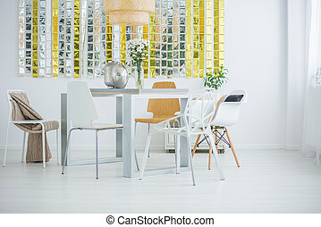 Room with communal table, chairs and wall decor