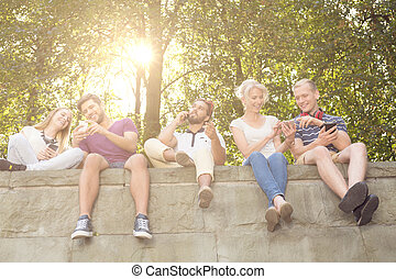 Looking at photos - Young students sitting together on the...