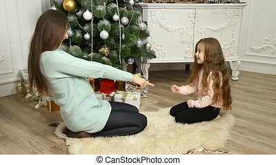 mother and daughter playing near the Christmas tree
