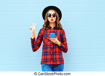 Fashion pretty cool young woman with smartphone blowing red lips making air kiss outdoors in city, wearing black hat and red checkered shirt