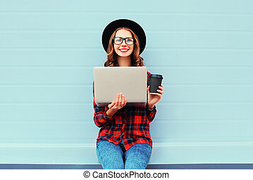 Fashion young smiling woman holding laptop computer with coffee cup resting outdoors in city, wearing black hat and red checkered shirt