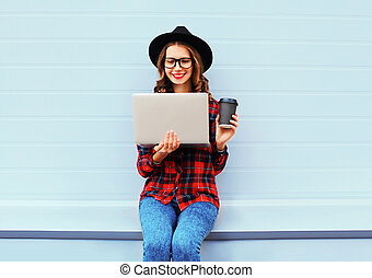 Fashion young smiling woman using laptop computer with coffee cup resting outdoors in city, wearing black hat and red checkered shirt