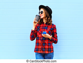 Fashion young smiling woman with coffee cup, smartphone outdoors in city, wearing a black hat red checkered shirt