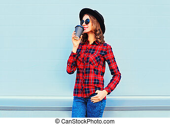 Fashion young woman with coffee cup resting outdoors in city, wearing black hat and red checkered shirt