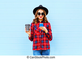 Fashion young woman with coffee cup resting using smartphone outdoors in city, wearing a black hat red checkered shirt