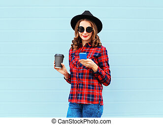 Fashion young woman with coffee cup resting using smartphone outdoors in city, wearing black hat red checkered shirt