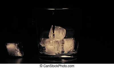 Slow mo whiskey in glass with ice on a black background