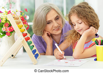 grandmother helping her granddaughter doing homework,...