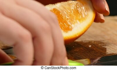Close-up. Orange, cut with a knife. - Women's hands with a...