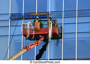 Construction Worker in Gondola with safety wear concept