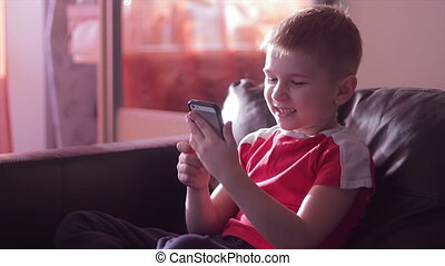 Young boy playing game on smartphone in home