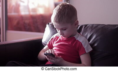 Young boy playing game on smartphone in home - Young boy...