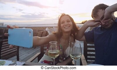 Young beautiful joyful couple in love takes selfie with smartphone having rest in outdoor cafe drinking wine at sunset time in slowmotion.
