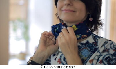 A brunette woman ties a blue scarf around his neck and...