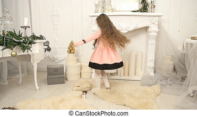 little girl turns and jumps in a white room