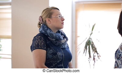 Woman in glasses and scarf stands and listens to the window....