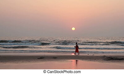 woman relaxing on the Goa beach in sunset rays