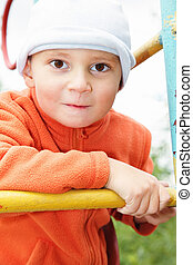 Funny kid in orange on climbing staircase