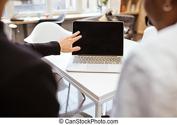 Cropped backview image of two young students using laptop -...