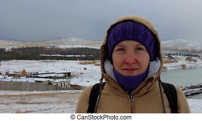 Portrait of a smiling girl in a jacket with a hood at the sea