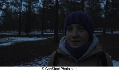 Portrait of a smiling girl in a cold dark winter forest -...