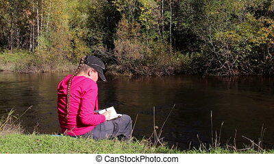 Girl in pink hoodie makes notes in a notebook sitting by the...