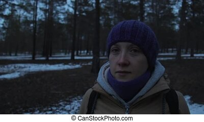 Girl looks around in the cold dark winter forest - Girl...
