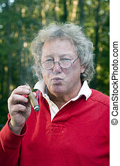 senior man smoking big cigar - senior man with long hair...