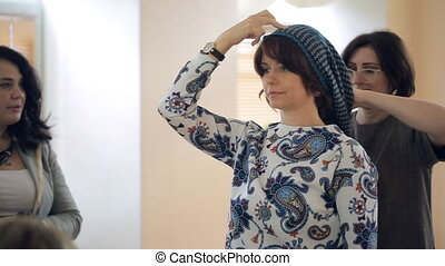stylist shows on model how to tie scarf on your head. It is...