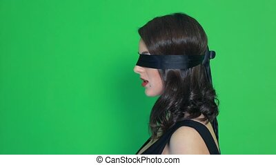 Blindfolded girl close-up green background