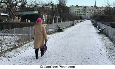 Senior woman is walking along the path in the allotments -...