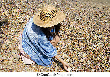 Asian thai woman sit and keep rock on stone beach at Koh Yao...