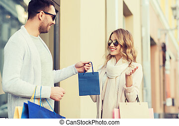 happy couple with shopping bags in city - sale, consumerism...