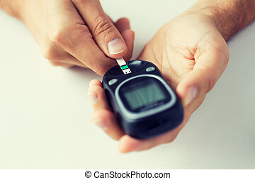 close up of man checking blood sugar by glucometer -...