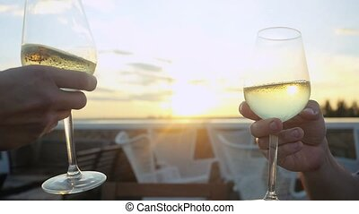 Group of people toasting and drinking wine on the restaurant terrace over sunset in slowmotion with lense flare effects. Celebrating. 1920x1080