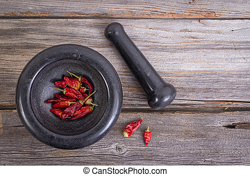 dried hot pepper with pestle and mortar on wooden plank...