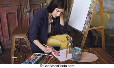 Young woman artist draw pictrure with watercolor paints and brush on easel canvas