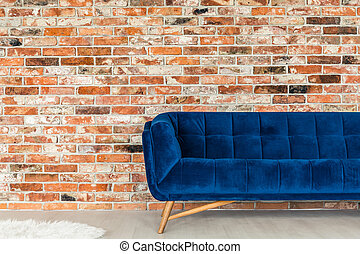 Blue upholstered sofa - Red brick wall and cobalt blue...