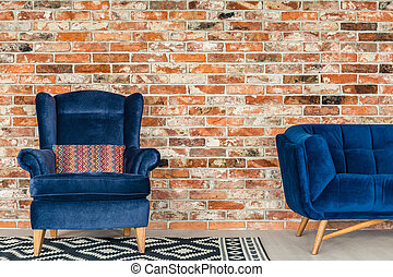 Blue upholstered armchair - Red brick wall, blue upholstered...
