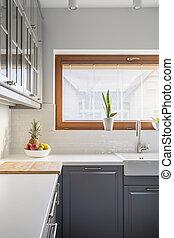 Modern kitchen with window, grey cupboard, white countertop...