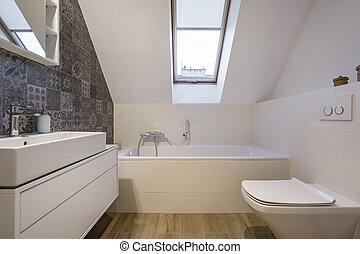 Attic bathroom with bathtub, window,, toilet and basin