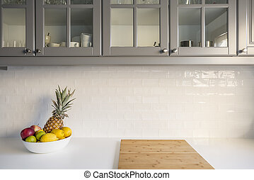 Kitchen with white worktop, grey furniture and brick tiles