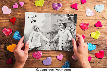 Hands holding picture of senior couple, colorful hearts....
