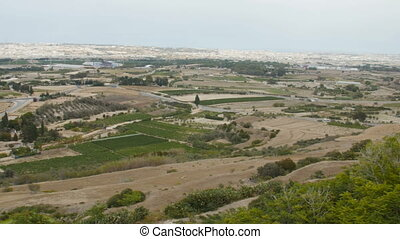 Panoramic view of Malta island agricultural fields, hills, roads and village.