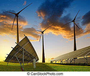 Solar panels with wind turbines at sunset.